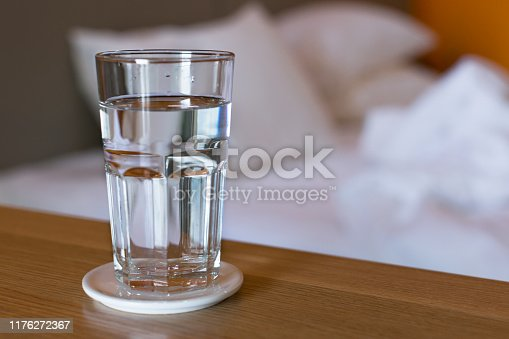 A glass of water sitting on a table next to a white bed in the morning, wake up routine.