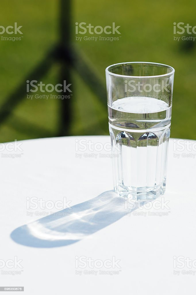 Glass of water lightened with sun on a white table royalty-free stock photo