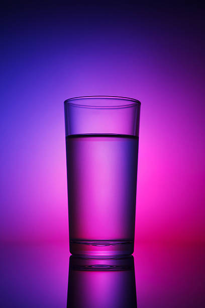 Glass of water lit with abstract backlight stock photo