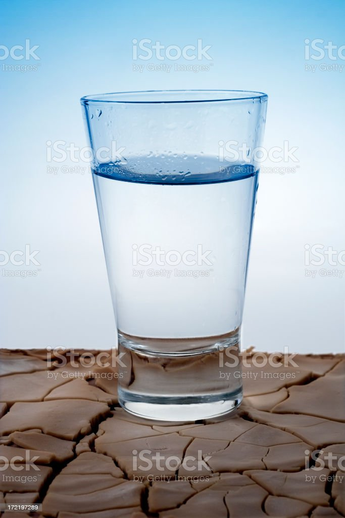 Glass of Water On Dry Rough Soil royalty-free stock photo