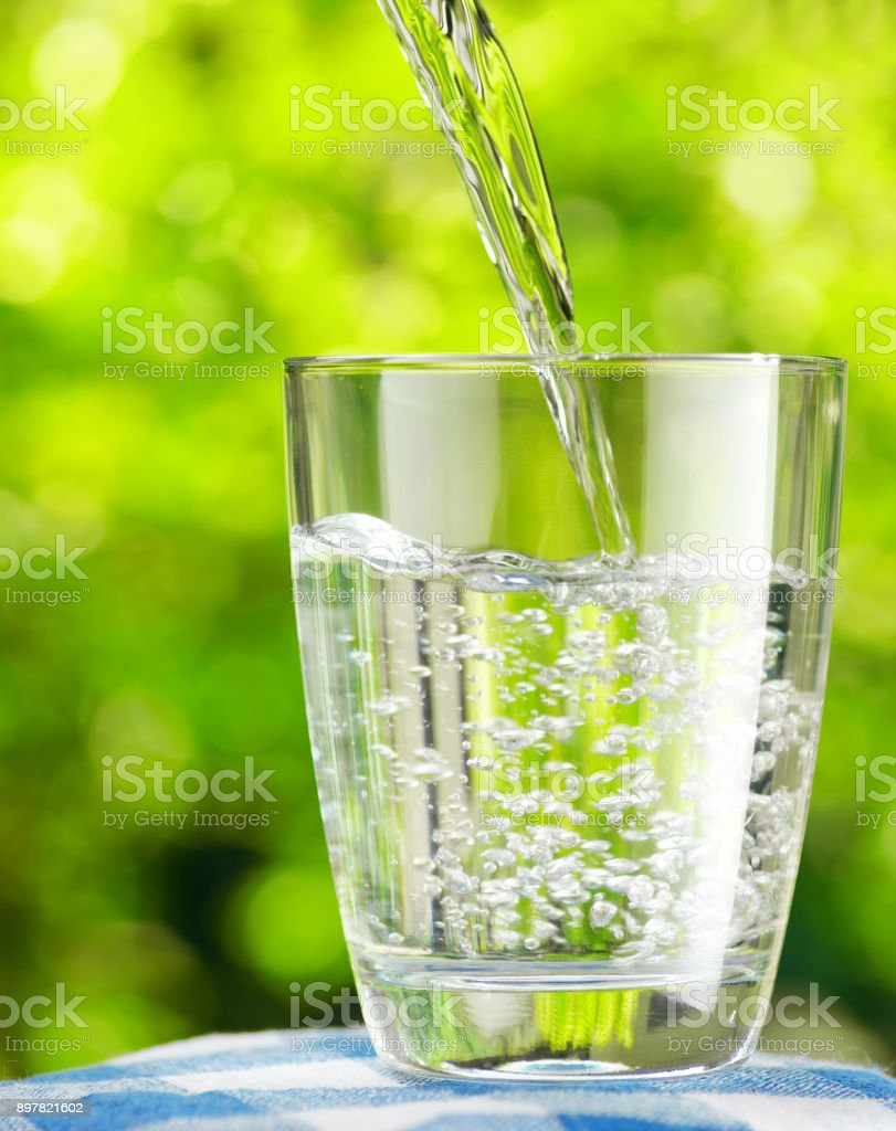 Glass of water on nature background stock photo