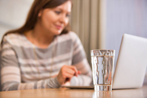 Glass of water on table against woman using laptop at home stock photo
