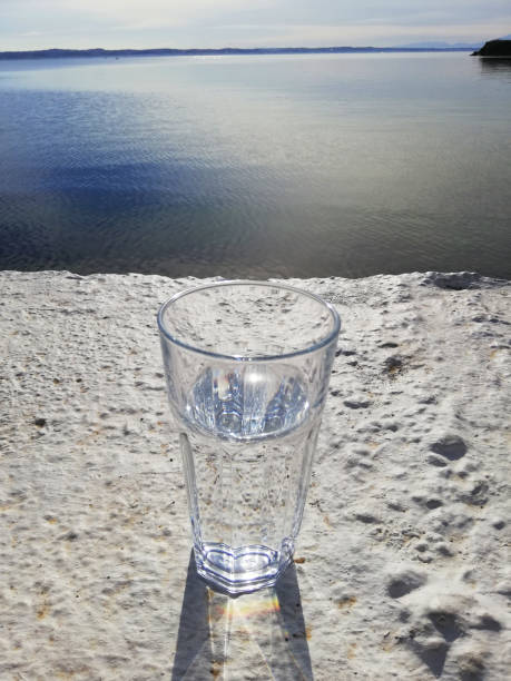 Glass of water on the beton with sea view stock photo