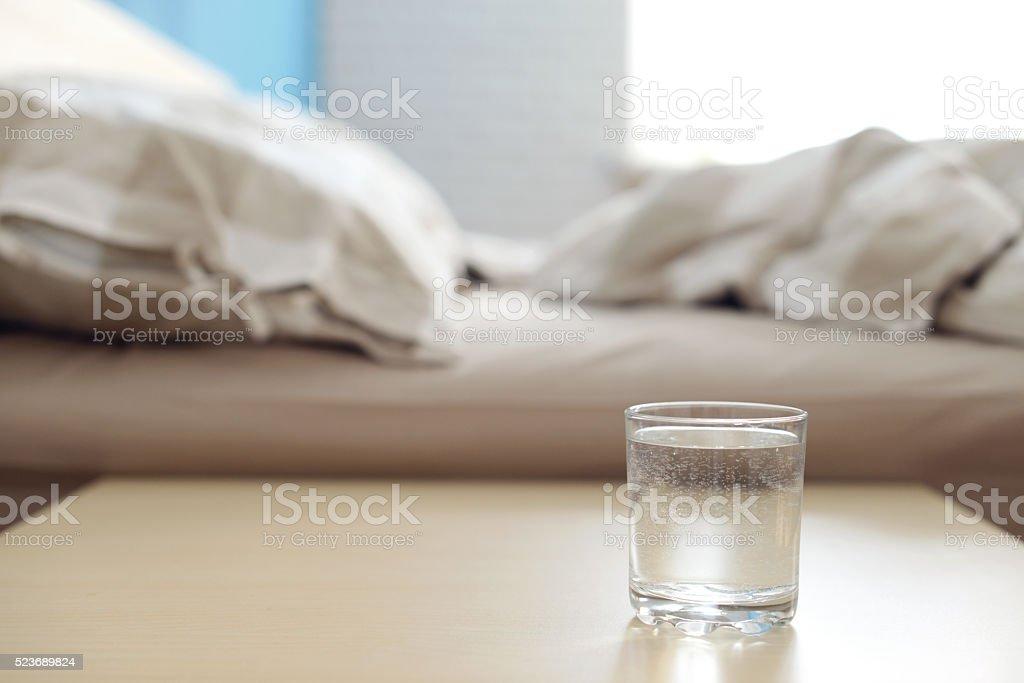 Glas von Wasser auf dem Nachttisch im Schlafzimmer Lizenzfreies stock-foto