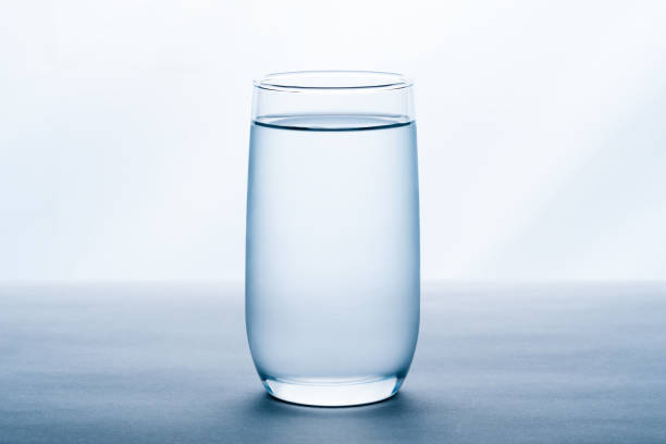 glass of water on white background. - glass stock photos and pictures