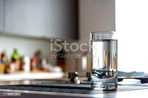 A glass filled with water atop a modern kitchen counter top inside a home.