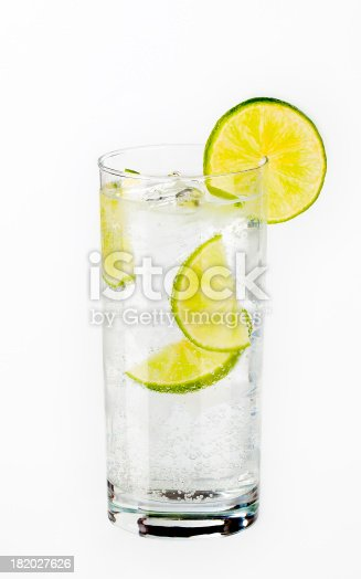 glass of water with ice cubes and slices of lime