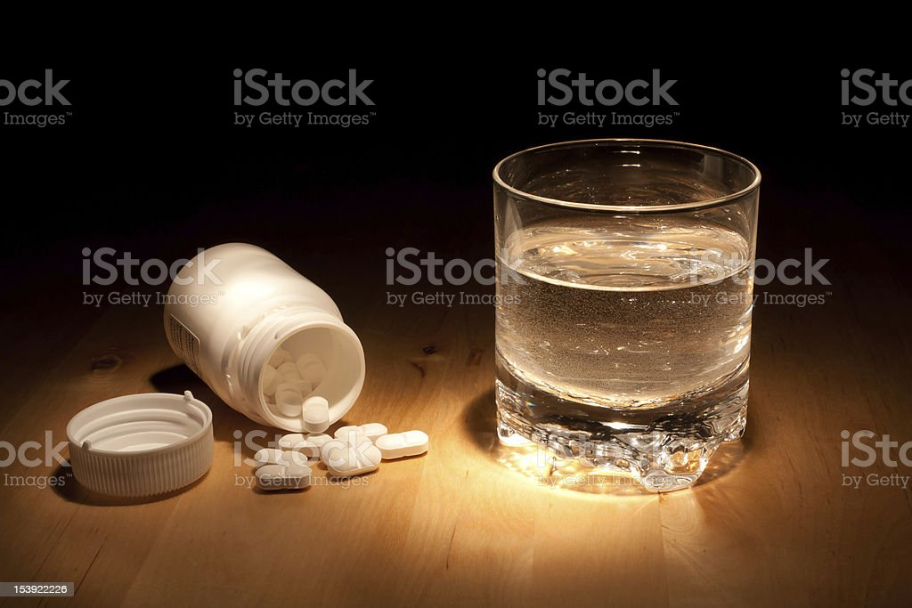A glass of water stood next to a jar of pills stock photo