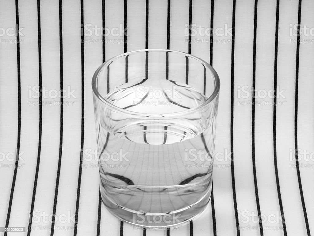 Glass of water. Symmetry, refraction. stock photo