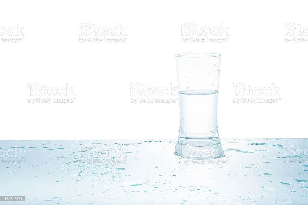 Glass of water with drops on light background royalty-free stock photo