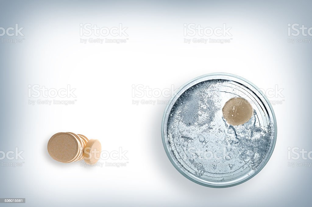 Glass of water with effervescent tablet top view stock photo