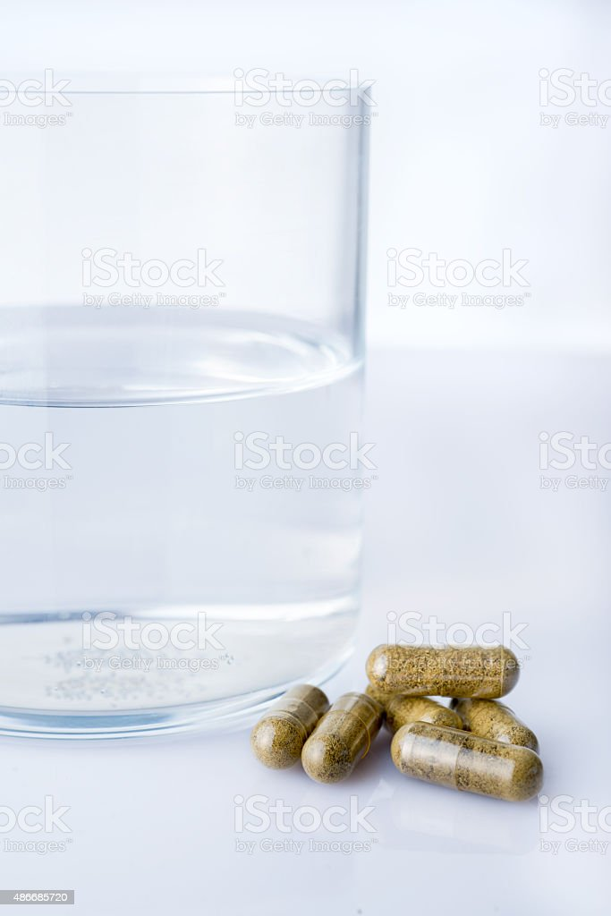 Glass of water with homepathy pills stock photo