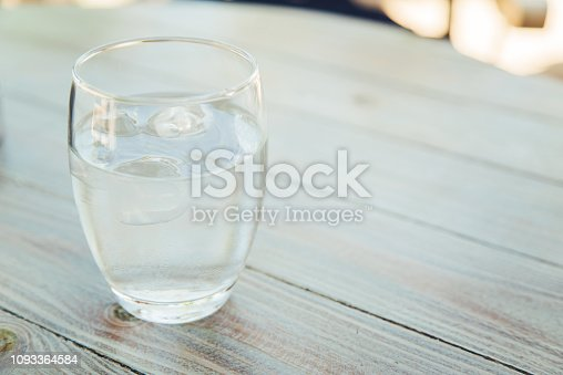 Close up of glass of water with ice on a wooden table