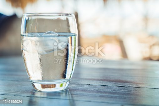 Close up of glass of water with ice on a wooden table.