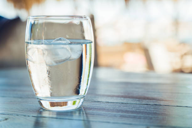 Glass of water with ice cubes stock photo