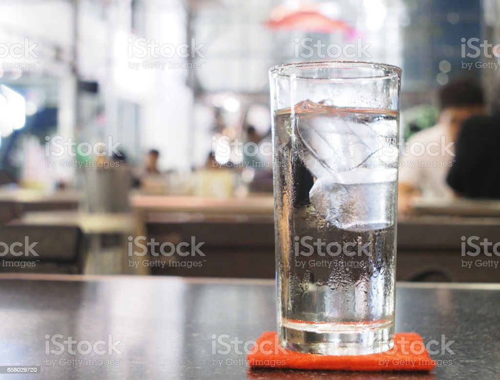 Glass of water with ice on the table in restaurant at night - foto stock
