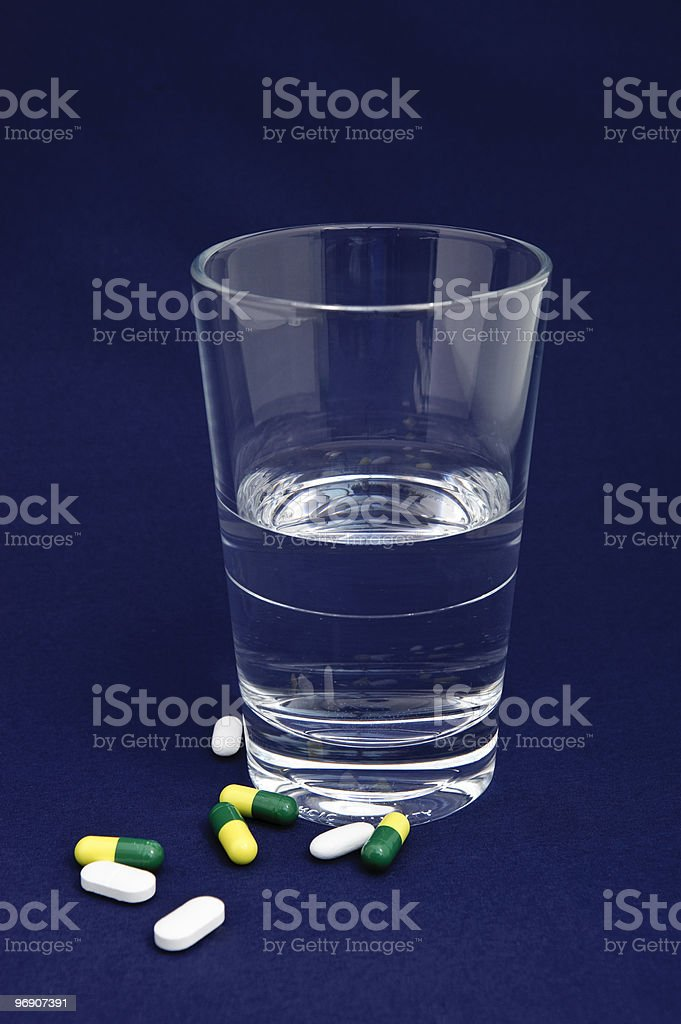 Glass of water with pills and capsules royalty-free stock photo