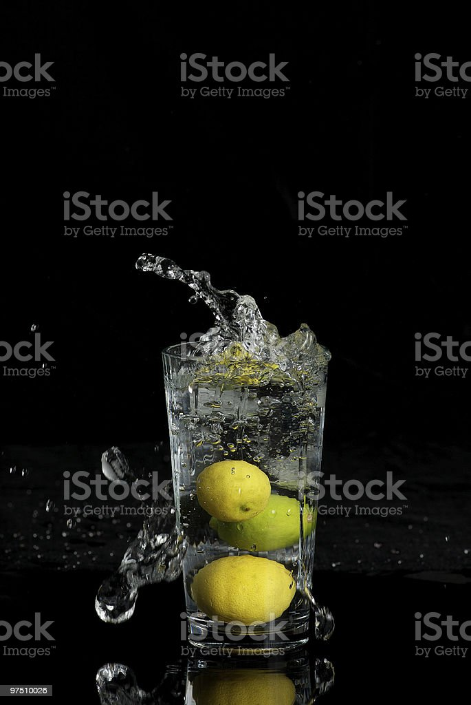 Glass of Water with Splashes and Limes royalty-free stock photo