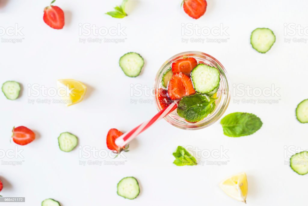 A glass of water with the addition of strawberries, cucumber, mint and lemon. Among the bright ingredients on a white background. Detox and Sports Concept. Top view, flat lay zbiór zdjęć royalty-free
