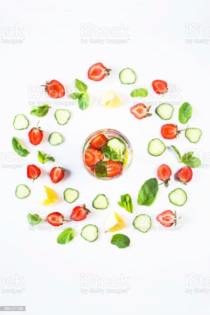 一杯水, 加上草莓, 黃瓜, 薄荷和檸檬。在一個白色的背景明亮的成分圈。排毒和體育概念。頂部視圖, 平躺 - 免版稅一片圖庫照片