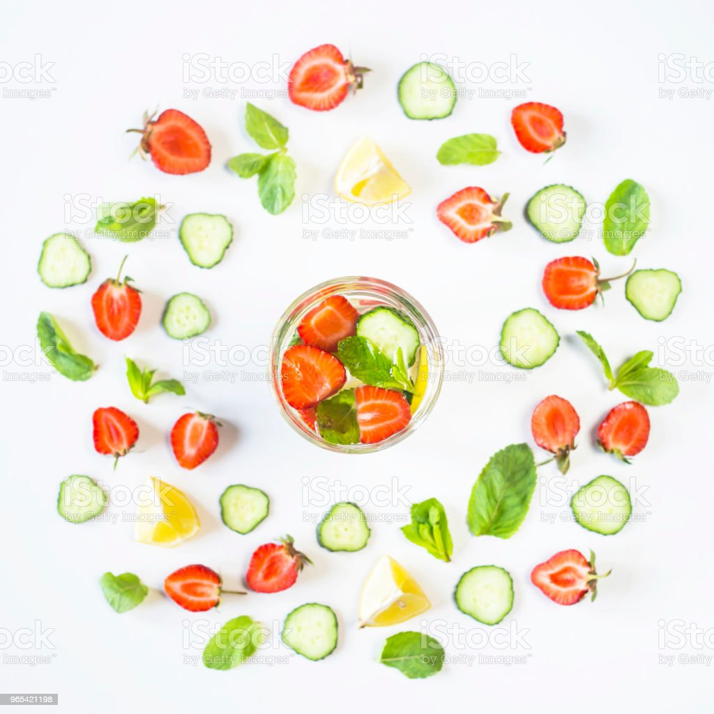 A glass of water with the addition of strawberries, cucumber, mint and lemon. In a circle of bright ingredients on a white background. Detox and Sports Concept. Top view, flat lay royalty-free stock photo