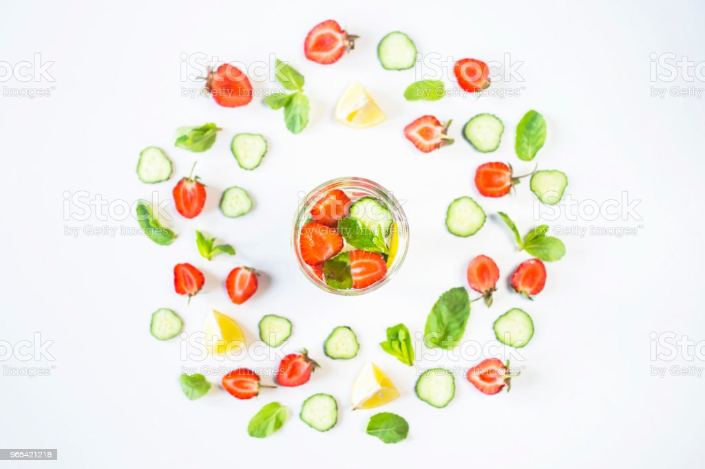 A glass of water with the addition of strawberries, cucumber, mint and lemon. In a circle of bright ingredients on a white background. Detox and Sports Concept. Top view, flat lay zbiór zdjęć royalty-free