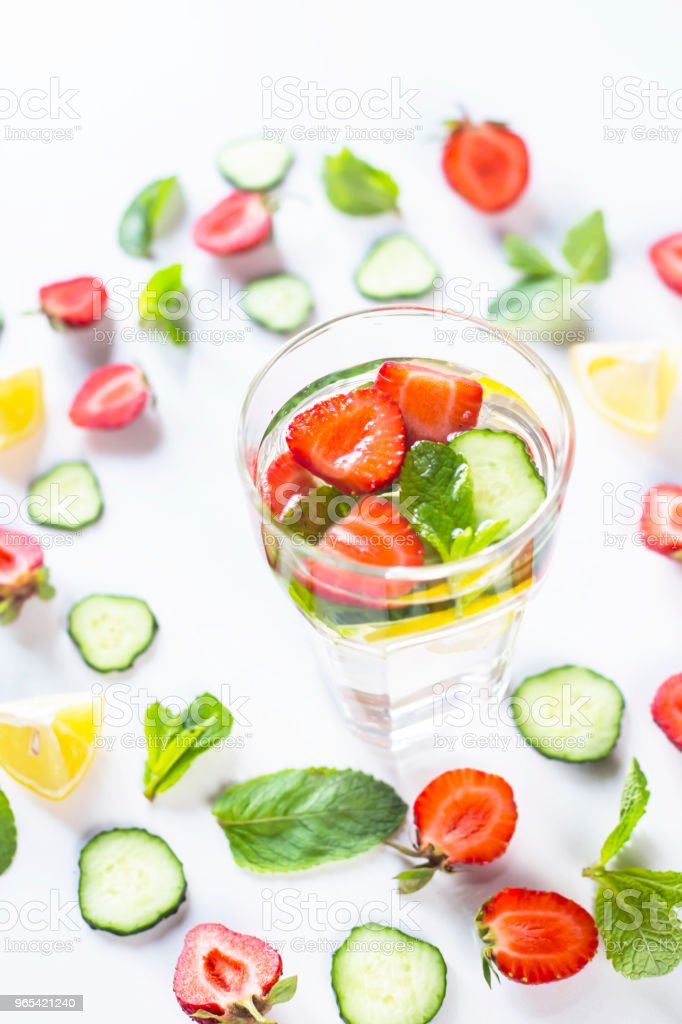 A glass of water with the addition of strawberries, cucumber, mint and lemon. In a circle of bright ingredients on a white background. Detox and Sports Concept royalty-free stock photo