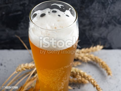 istock A glass of wheat beer on a dark concrete background and wheat ears 1165341099