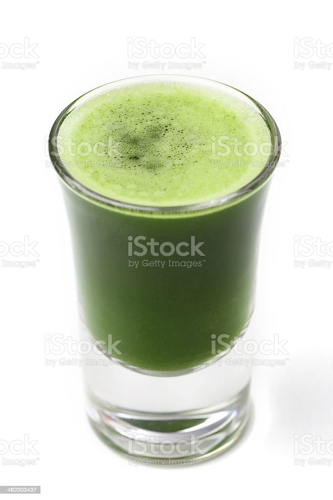 Glass of wheat grass juice on white background stock photo
