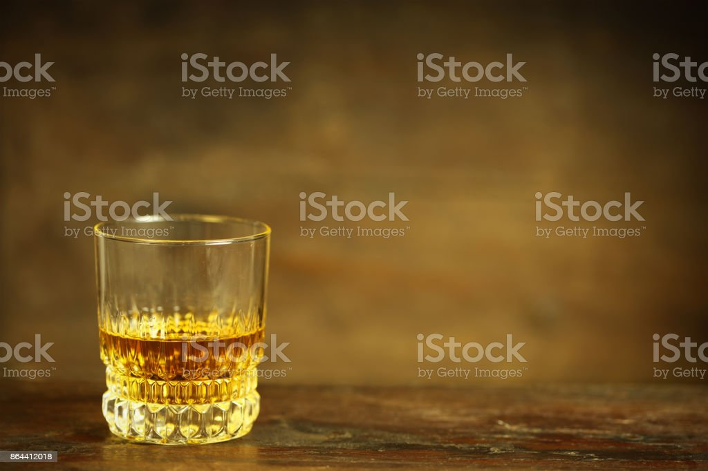Glass of Whiskey Against Dark Rustic Background stock photo