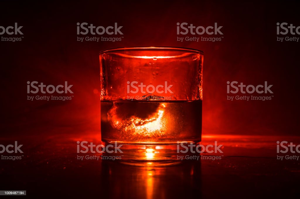Glass of whiskey and ice on wooden surface with color light and fog on background. Copy space. Advertising shot stock photo