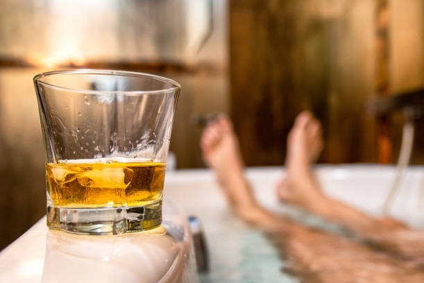 Glass of whiskey and legs on bathtub stock photo