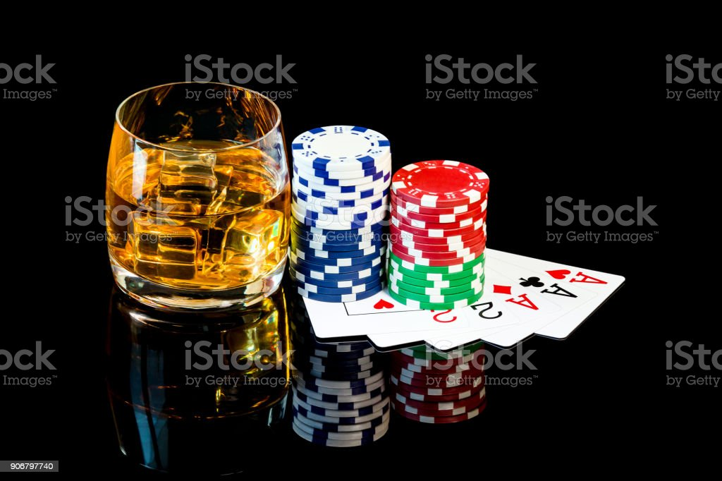 Glass of whiskey and poker cards with color chips stock photo