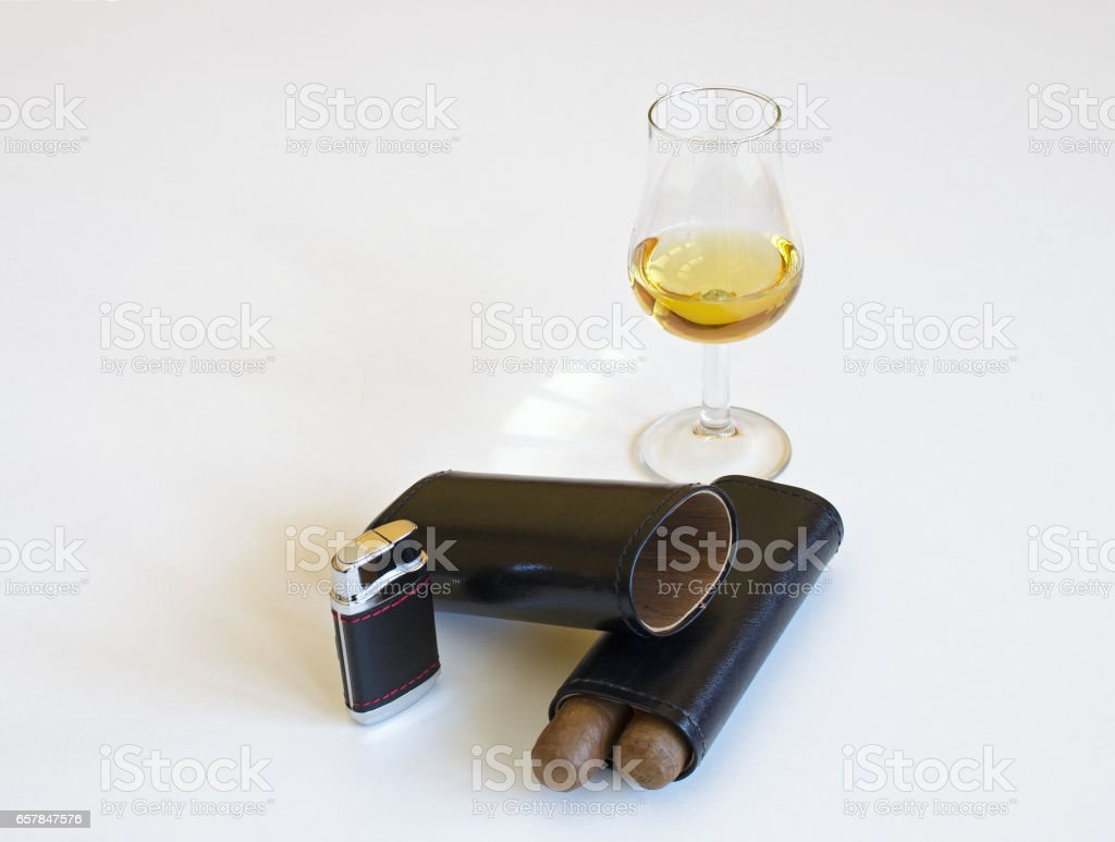 Glass of whiskey and two cigars, leather and black, cigar lighter stock photo