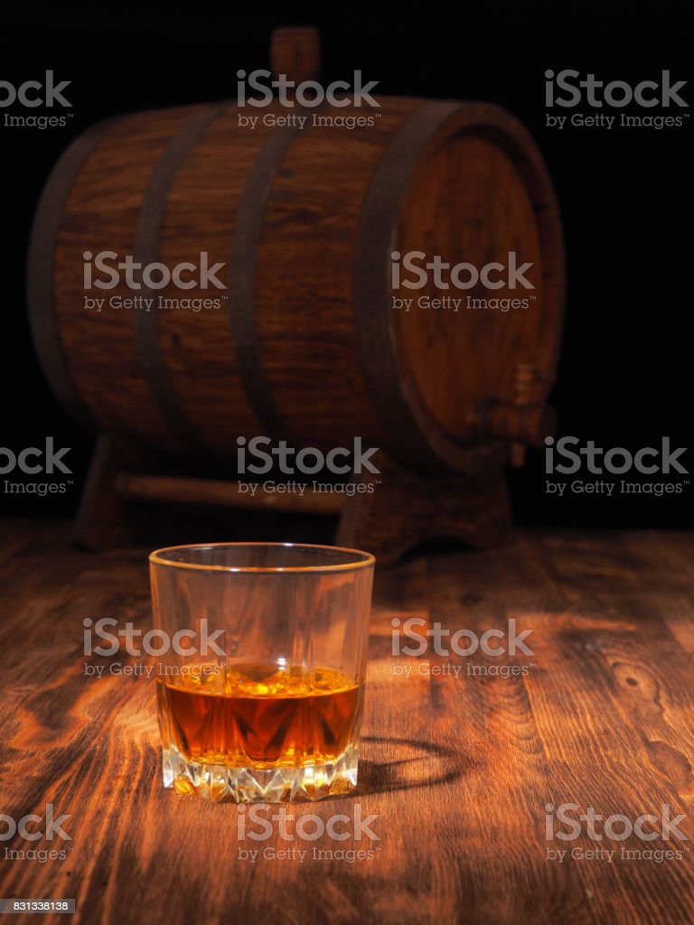 Glass of whiskey and vintage wooden barrel stock photo