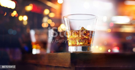 istock Glass of whiskey drink with ice cube on table wooden bar background 857015412