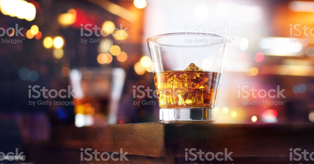 Glass of whiskey drink with ice cube on table wooden bar background stock photo
