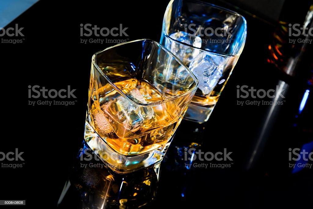 Un verre de whisky de bouteille sur table noir avec reflet - Photo