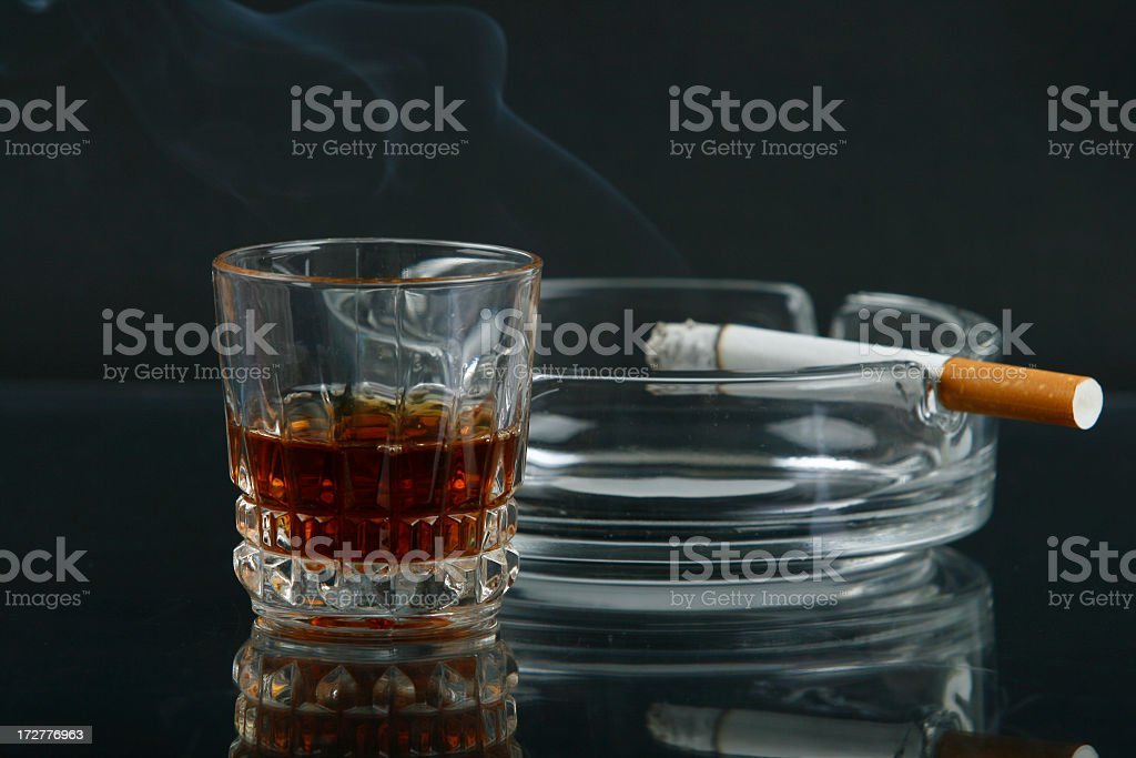 Glass of whiskey next to a cigarette in an ash tray stock photo
