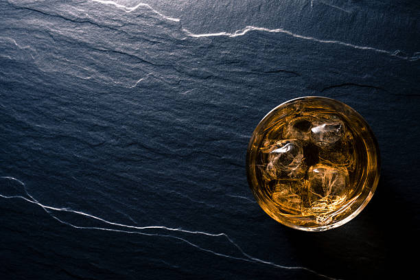 glass of whiskey on dark table - whiskey stock photos and pictures