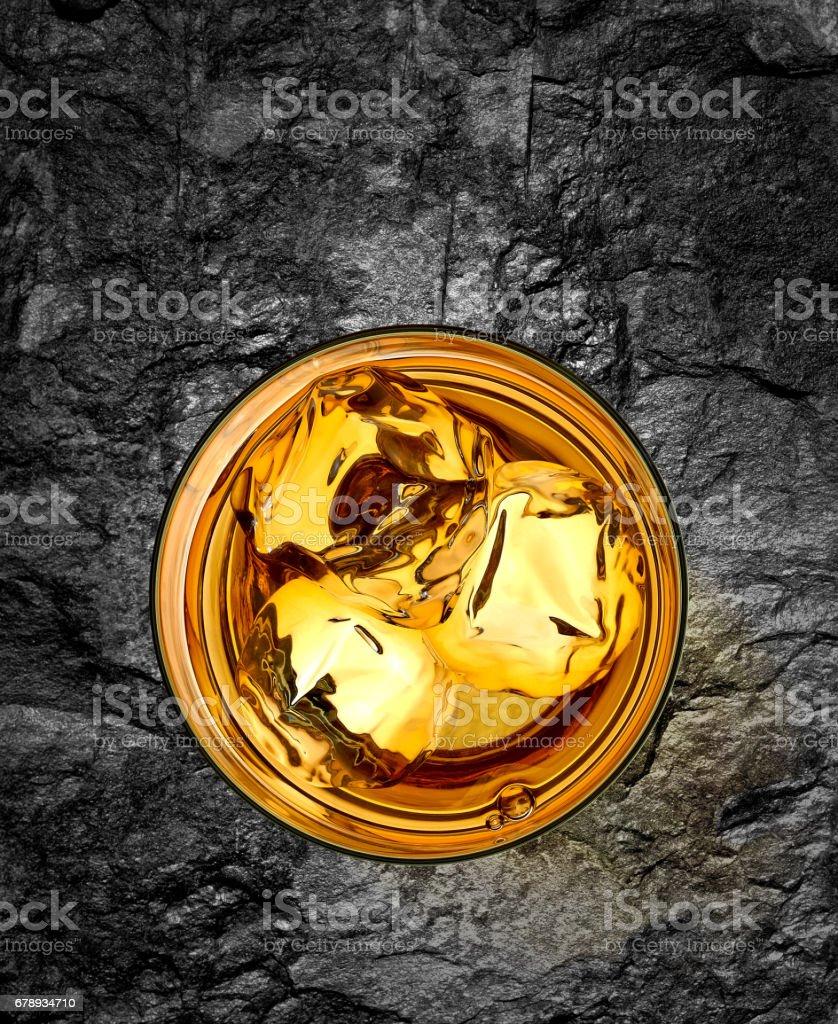 Glass of whiskey on stone background stock photo