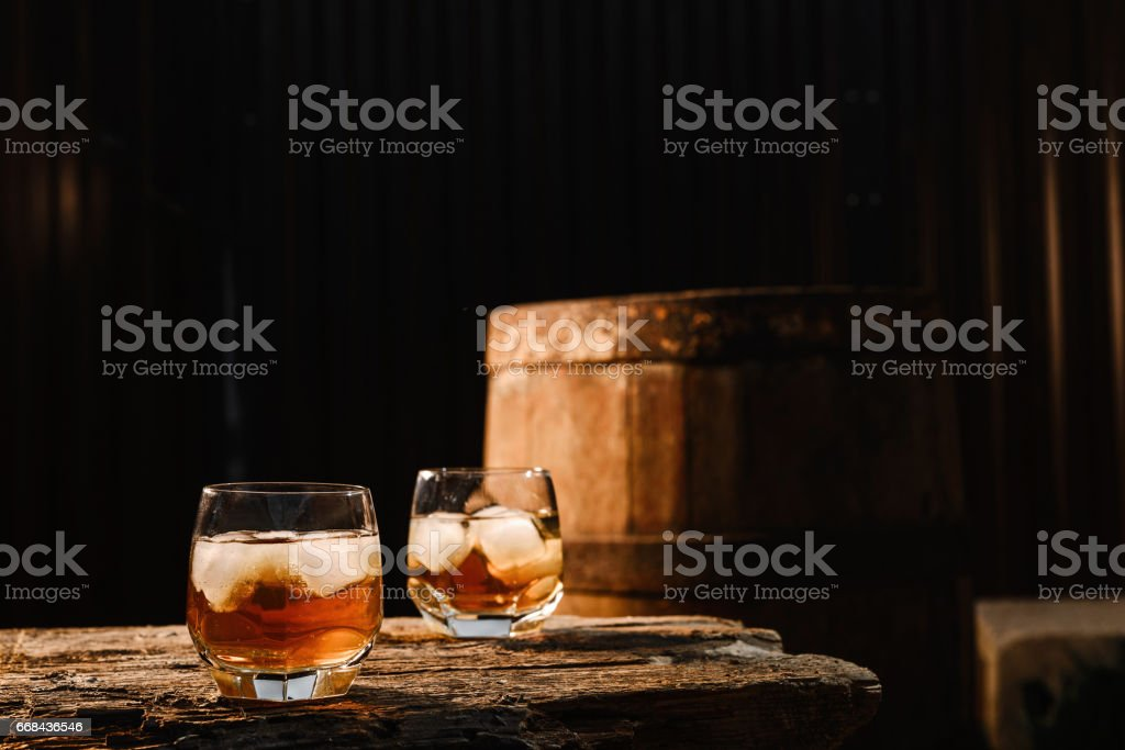 Glass of whiskey on wooden background close up stock photo