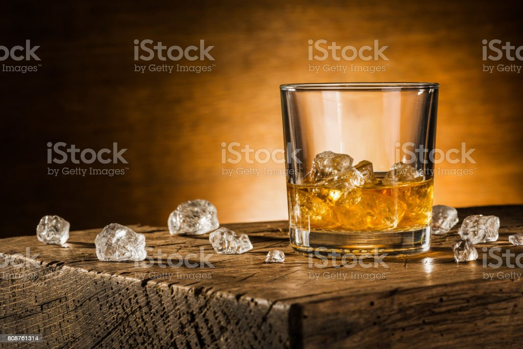 Glass of whiskey on wooden background stock photo