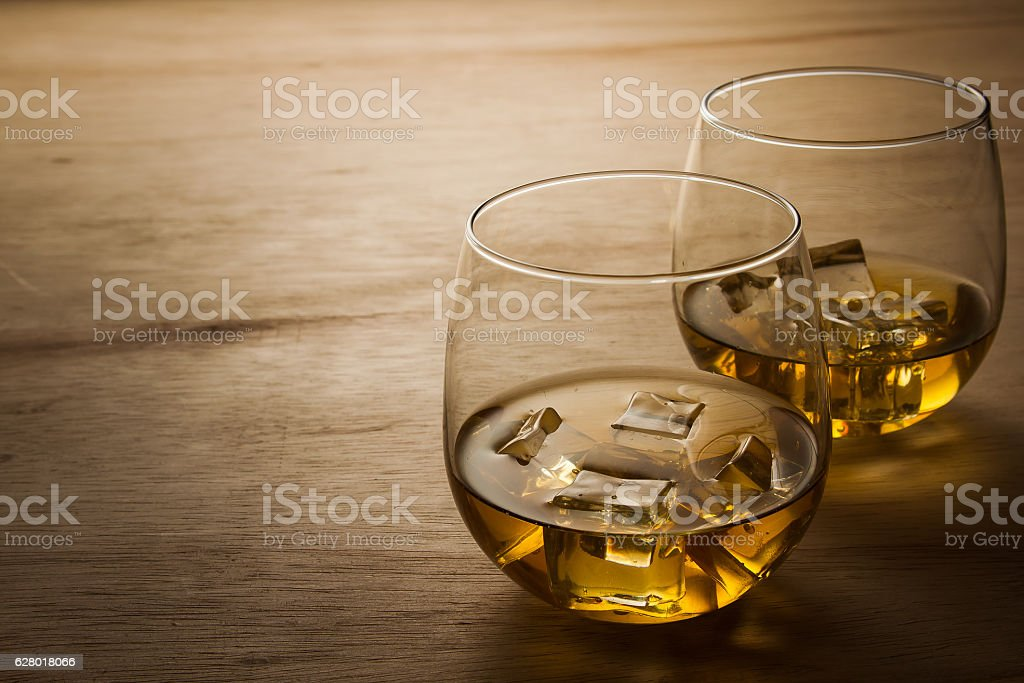 glass of whiskey on wooden table stock photo