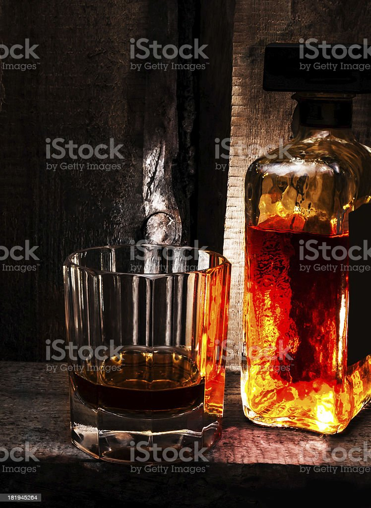 Glass of Whiskey Scotch and  bottle on old wooden background. stock photo
