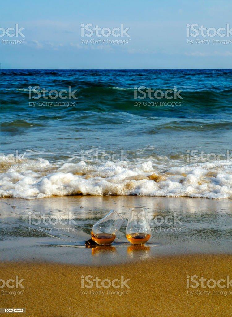 copo de uísque de malte na areia lavada pelas ondas, um copo de degustação, relaxe na praia - Foto de stock de Amarelo royalty-free