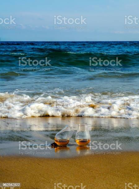 Foto de Copo De Uísque De Malte Na Areia Lavada Pelas Ondas Um Copo De Degustação Relaxe Na Praia e mais fotos de stock de Amarelo