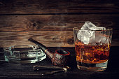 Glass of whiskey with ice and pipe