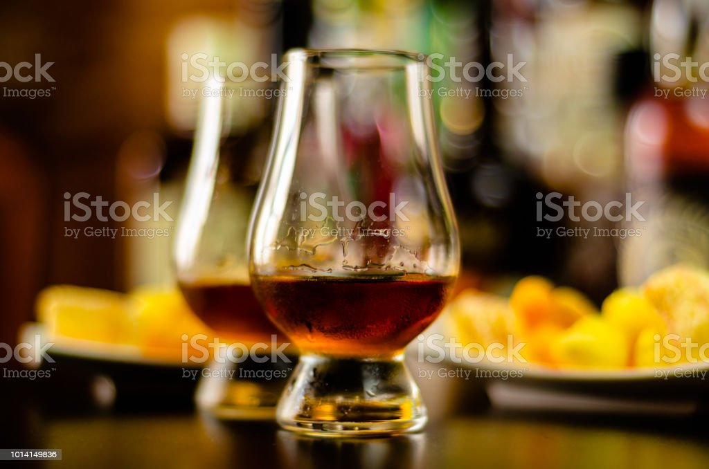 glass of whiskey with ice cubes and salty snacks on the background of the bar, stock photo
