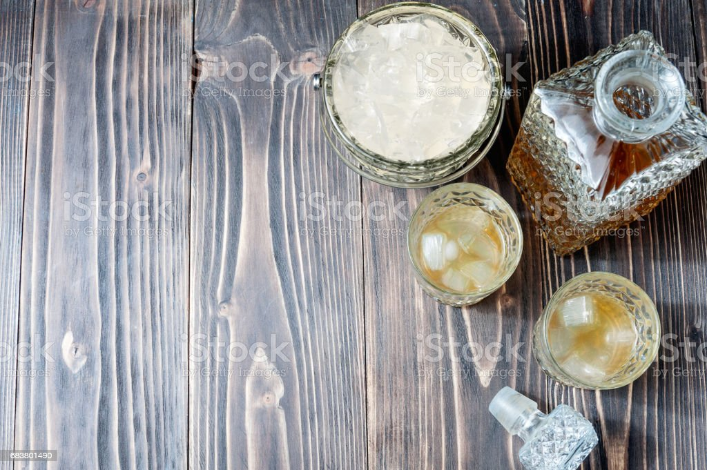 Glass of whiskey with ice cubes and whiskey bottle on an old wooden table stock photo